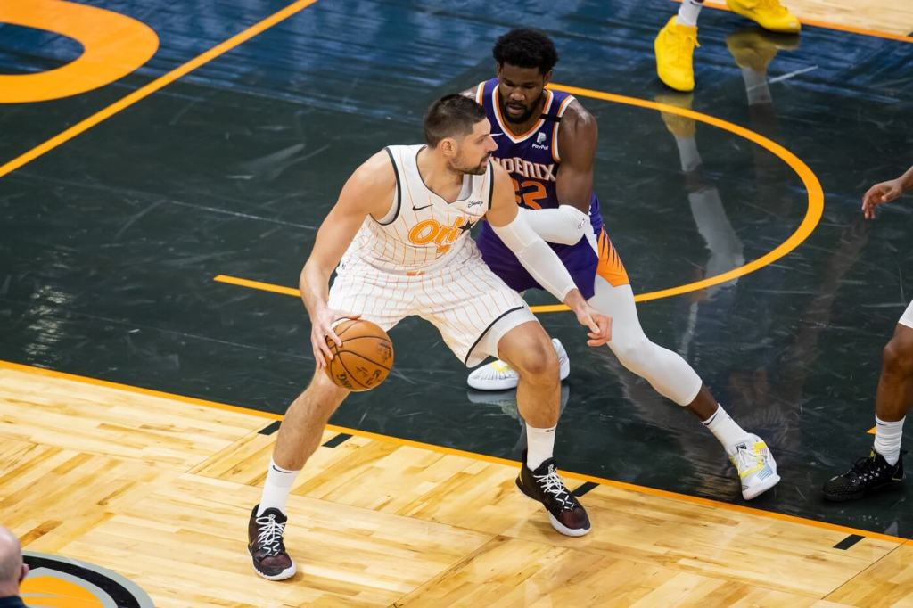 Orlando Magic center Nikola Vucevic (9) drives past Phoenix Suns center Deandre Ayton (22) during the fourth quarter of a game at Amway Center.