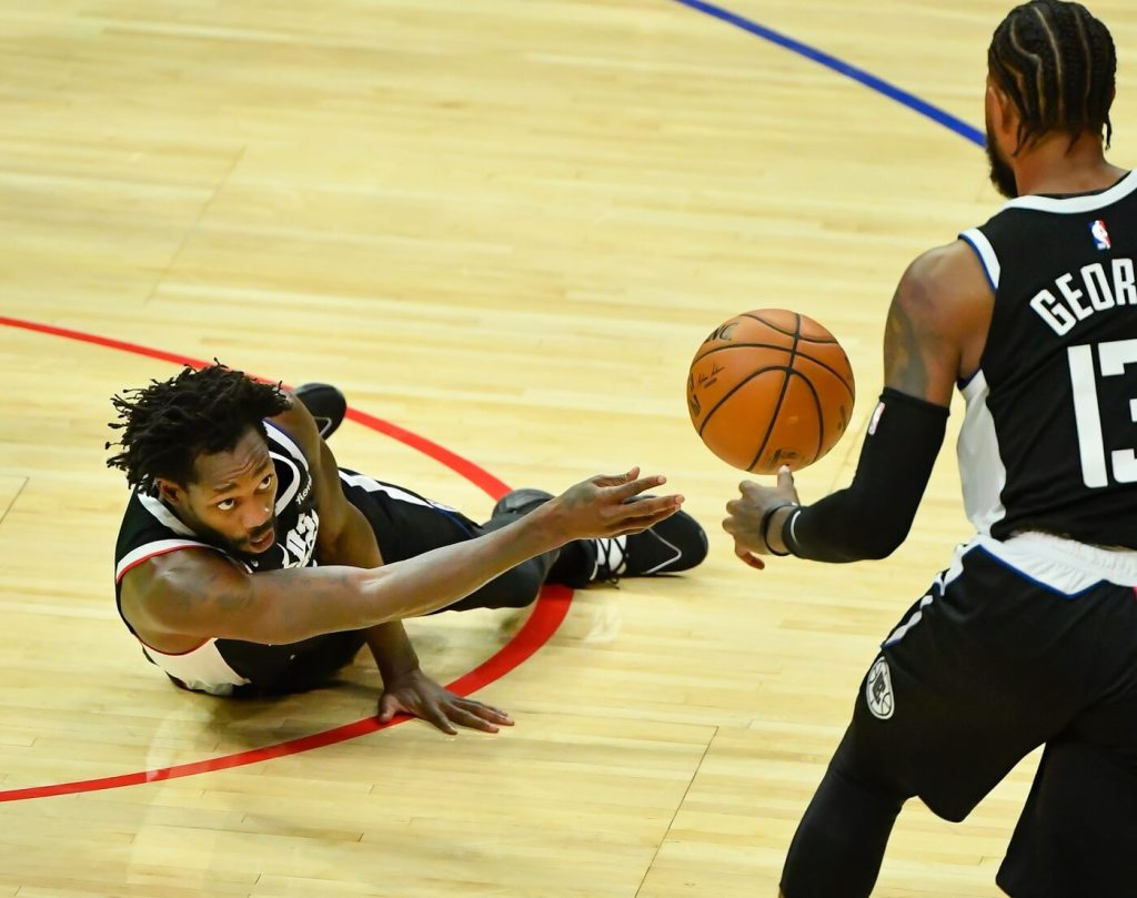 Jan 22, 2021; Los Angeles, California, USA; LA Clippers guard Patrick Beverly goes to the floor for a loose ball and pushes the ball to teammate Paul George (13) during the third quarter against the Oklahoma City Thunder at Staples Center. Mandatory Credit: Robert Hanashiro-USA TODAY Sports