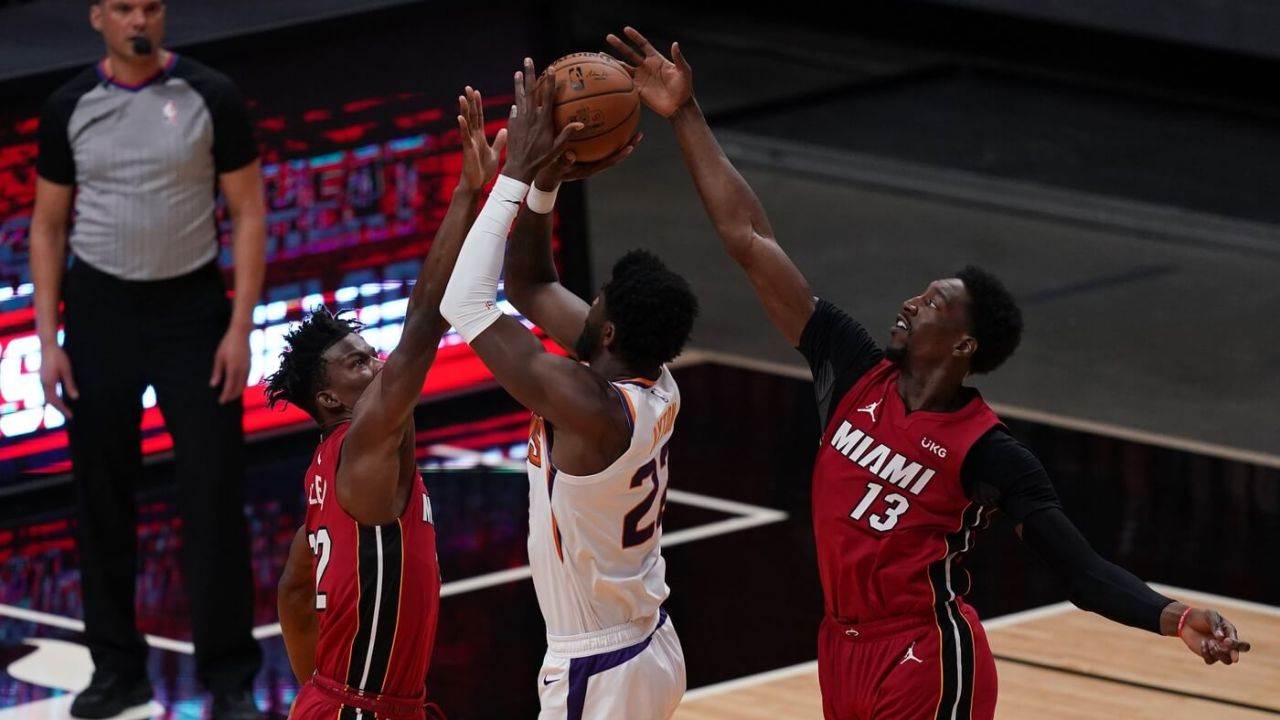 Mar 23, 2021; Miami, Florida, USA; Phoenix Suns center Deandre Ayton (22) attempts to shoot the ball between Miami Heat forward Jimmy Butler (22) and center Bam Adebayo (13) during the first half at American Airlines Arena. Mandatory Credit: Jasen Vinlove-USA TODAY Sports