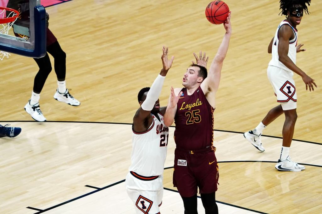 Mar 21, 2021; Indianapolis, Indiana, USA; Loyola Ramblers center Cameron Krutwig (25) shoots over Illinois Fighting Illini center Kofi Cockburn (21)during the first half in the second round of the 2021 NCAA Tournament at Bankers Life Fieldhouse. Mandatory Credit: Kirby Lee-USA TODAY Sports