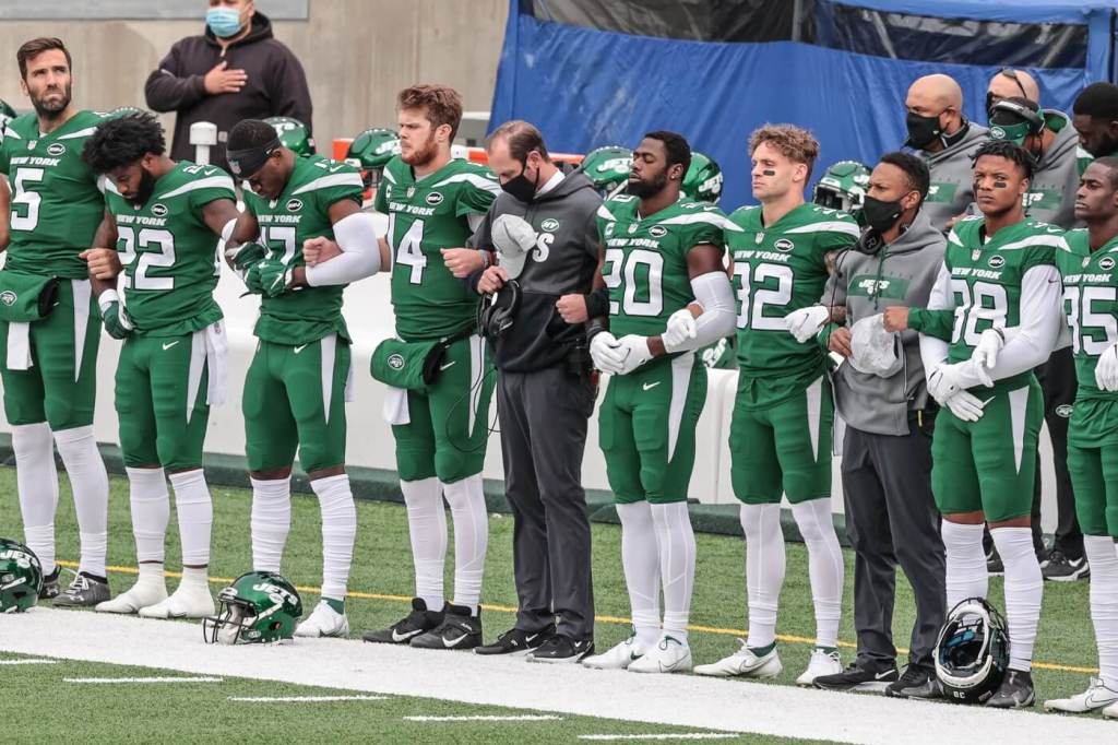 New York Jets head coach Adam Gase joins arms with players including quarterback Sam Darnold (14) and free safety Marcus Maye (20) during the playing of the national anthem before their game against the Buffalo Bills at MetLife Stadium