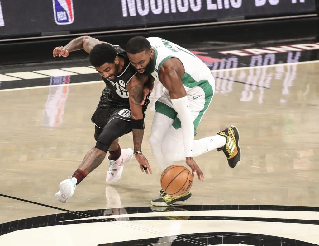 Mar 11, 2021; Brooklyn, New York, USA; Brooklyn Nets guard Kyrie Irving (11) and Boston Celtics guard Jaylen Brown (7) go after a loose ball in the first quarter at Barclays Center. Mandatory Credit: Wendell Cruz-USA TODAY Sports