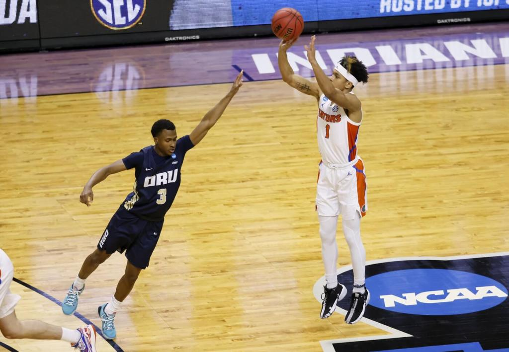 Florida Gators guard Tre Mann (1) shoots a jumper over Oral Roberts Golden Eagles guard Max Abmas (3) in the second half during the second round of the 2021 NCAA Tournament on Sunday, March 21, 2021, at Indiana Farmers Coliseum in Indianapolis, Ind