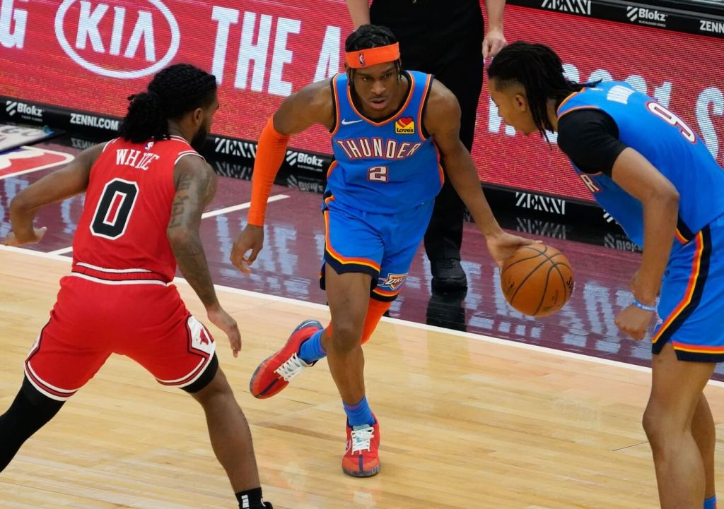 Mar 16, 2021; Chicago, Illinois, USA; Oklahoma City Thunder guard Shai Gilgeous-Alexander (2) moves the ball away from Chicago Bulls guard Coby White (0) and Oklahoma City Thunder center Moses Brown (9) during the second half at the United Center. Mandatory Credit: Matt Marton-USA TODAY Sports