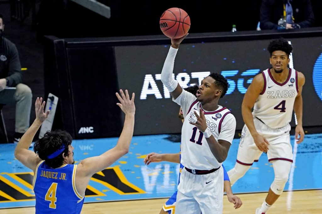 Gonzaga Bulldogs guard Joel Ayayi (11) shoots the ball against UCLA Bruins guard Jaime Jaquez Jr. (4) during the second half in the national semifinals of the Final Four of the 2021 NCAA Tournament at Lucas Oil Stadium.