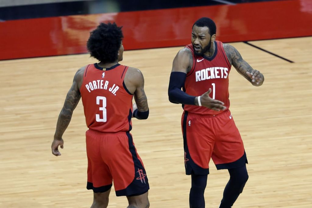 Apr 7, 2021; Houston, Texas, USA; Houston Rockets guard Kevin Porter Jr. (3) and guard John Wall (1) celebrate after Wall scored in the final minute during the second half of an NBA basketball game against the Dallas Mavericks at Toyota Center. Mandatory Credit: Michael Wyke/POOL PHOTOS-USA TODAY Sports