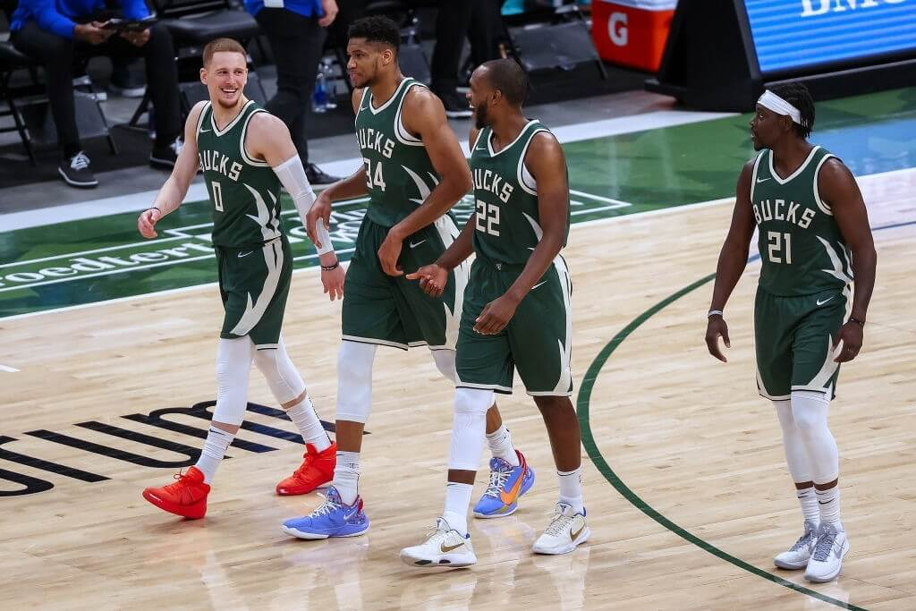 MILWAUKEE, WISCONSIN - MARCH 20: Donte DiVincenzo #0, Giannis Antetokounmpo #34, Khris Middleton #22, and Jrue Holiday #21 of the Milwaukee Bucks walk across the court in the third quarter against the San Antonio Spurs at the Fiserv Forum on March 20, 2021 in Milwaukee, Wisconsin. NOTE TO USER: User expressly acknowledges and agrees that, by downloading and or using this photograph, User is consenting to the terms and conditions of the Getty Images License Agreement. (Photo by Dylan Buell/Getty Images)