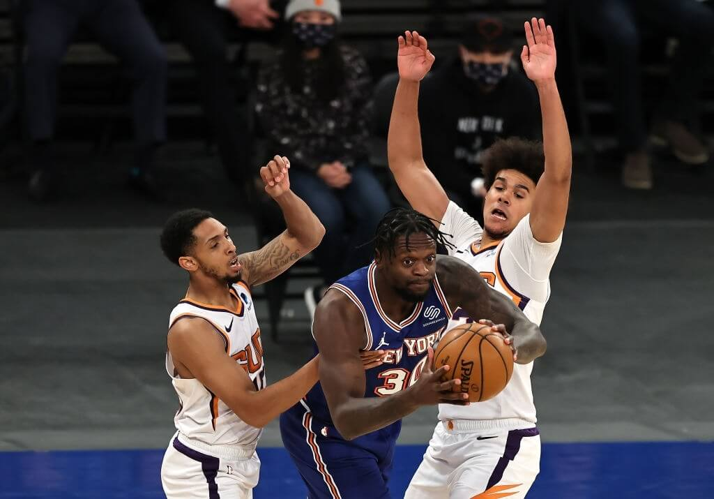 NEW YORK, NEW YORK - APRIL 26: Julius Randle #30 of the New York Knicks looks to pass as Cameron Payne #15 and Cameron Johnson #23 of the Phoenix Suns defend in the first pahf at Madison Square Garden on April 26, 2021 in New York City. NOTE TO USER: User expressly acknowledges and agrees that, by downloading and or using this photograph, User is consenting to the terms and conditions of the Getty Images License Agreement. (Photo by Elsa/Getty Images)