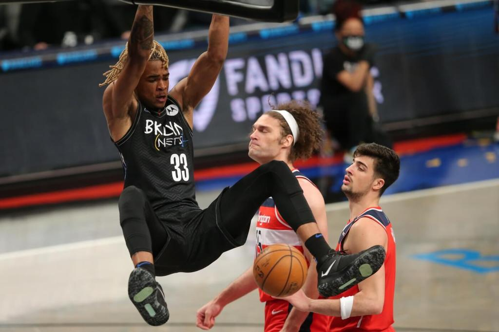 Mar 21, 2021; Brooklyn, New York, USA; Brooklyn Nets power forward Nicolas Claxton (33) dunks against Washington Wizards center Robin Lopez (15) and small forward Deni Avdija (9) during the first quarter at Barclays Center. Mandatory Credit: Brad Penner-USA TODAY Sports