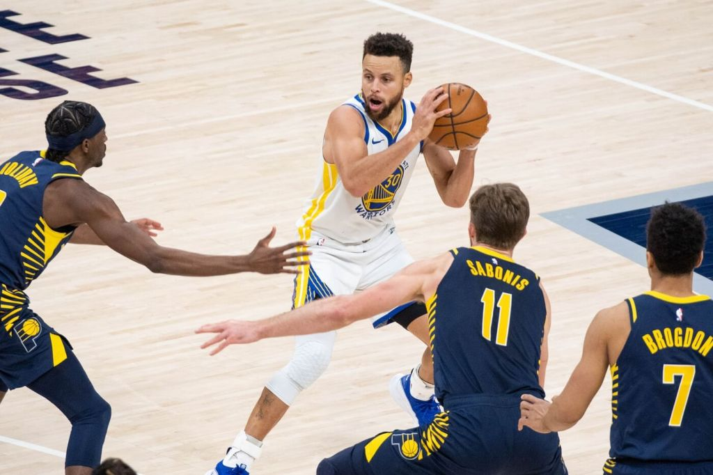 Feb 24, 2021; Indianapolis, Indiana, USA; Golden State Warriors guard Stephen Curry (30) looks to pass the ball away from the Indiana Pacers defense in the fourth quarter at Bankers Life Fieldhouse. Mandatory Credit: Trevor Ruszkowski-USA TODAY Sports