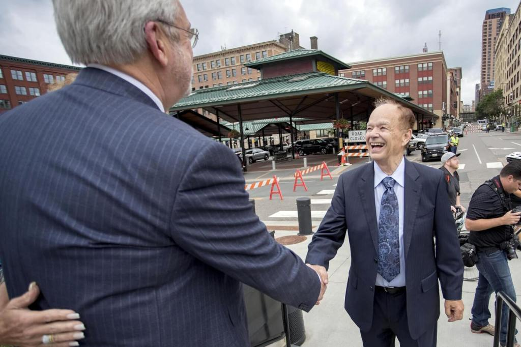 Aug 19, 2016; St. Paul, MN, USA; Minnesota United owner Bill McGuire (left) shakes hands with another Minnesota United owner Glen Taylor (right) during a press conference at CHS Field. Mandatory Credit: Jesse Johnson-USA TODAY Sports