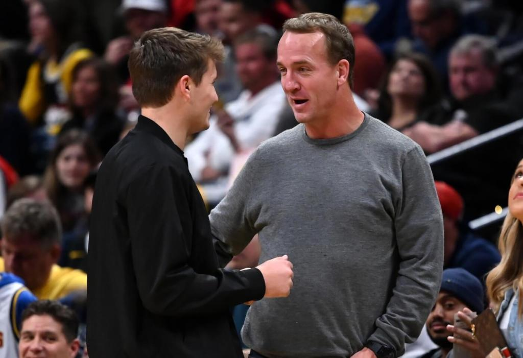 Denver Broncos quarterback Drew Lock talks with retired NFL quarterback Peyton Manning during the game between the Toronto Raptors against the Denver Nuggets at the Pepsi Center. Credit: Ron Chenoy