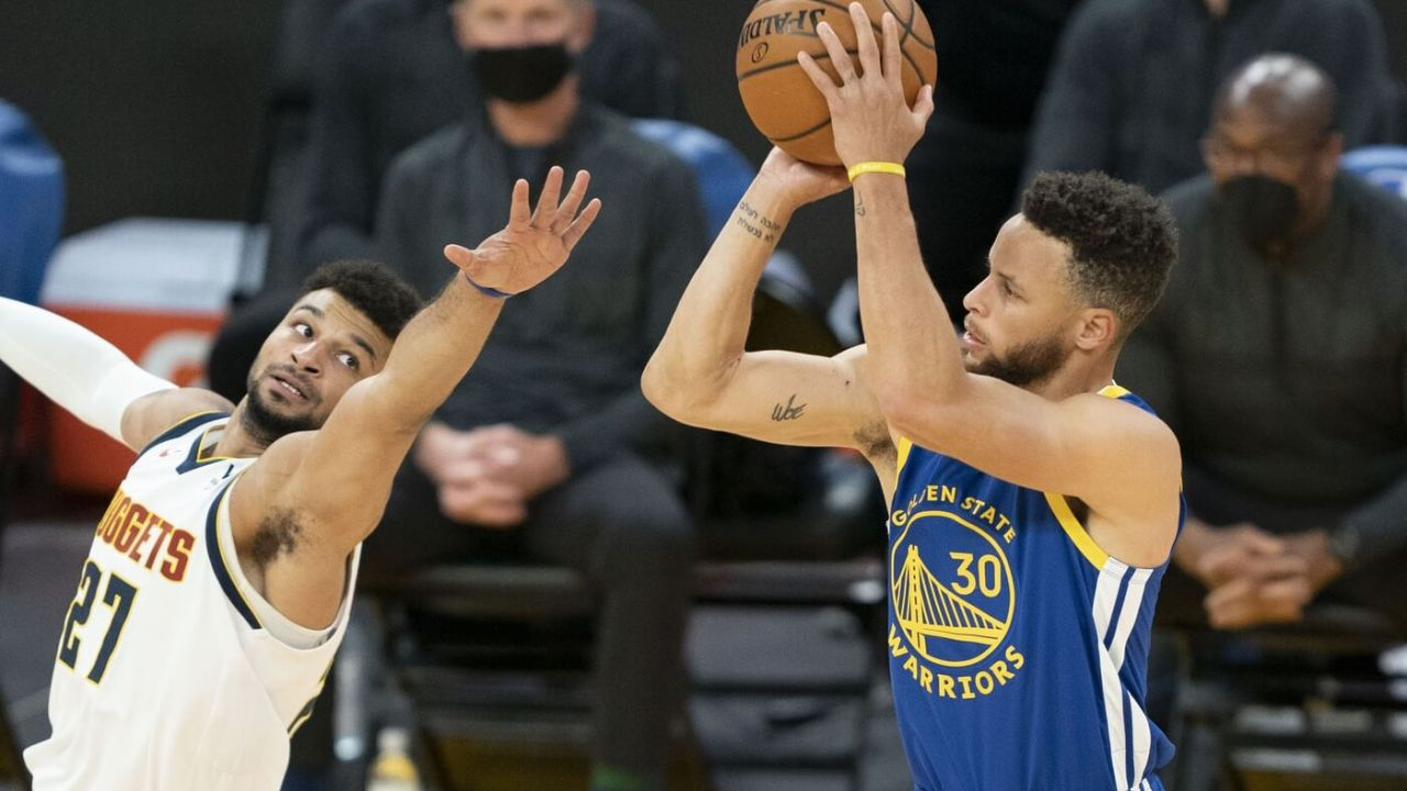 April 12, 2021; San Francisco, California, USA; Golden State Warriors guard Stephen Curry (30) shoots the basketball against Denver Nuggets guard Jamal Murray (27) during the first quarter at Chase Center. Mandatory Credit: Kyle Terada-USA TODAY Sports