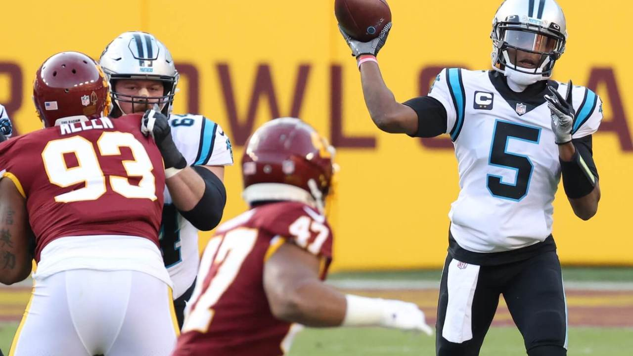 Dec 27, 2020; Landover, Maryland, USA; Carolina Panthers quarterback Teddy Bridgewater (5) passes the ball under pressure from Washington Football Team defensive tackle Jonathan Allen (93) in the first quarter at FedExField. Mandatory Credit: Geoff Burke-USA TODAY Sports