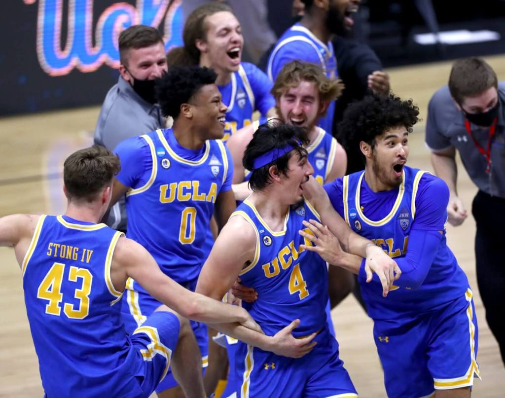 UCLA players celebrate after defeating Michigan during the Elite Eight round of the 2021 NCAA Tournament on Wednesday, March 31, 2021, at Lucas Oil Stadium in Indianapolis, Ind. Ncaa Basketball Ncaa Tournament Michigan Vs Ucla