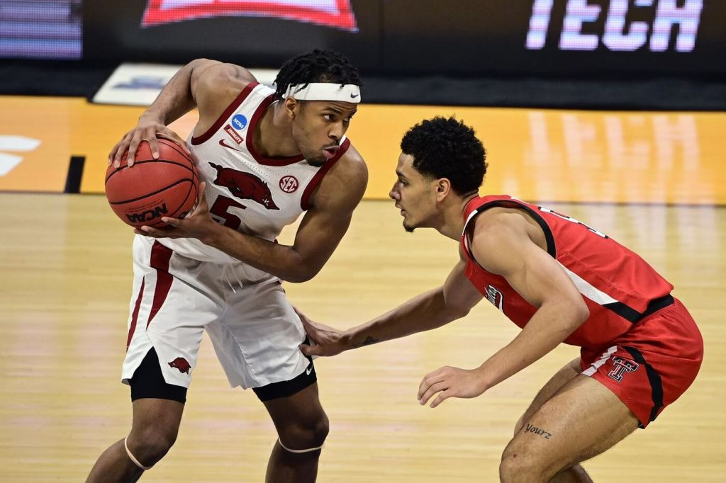 Mar 21, 2021; Indianapolis, Indiana, USA; Arkansas Razorbacks guard Moses Moody (5) holds the ball away from Texas Tech Red Raiders guard Micah Peavy (5) in the first half in the second round of the 2021 NCAA Tournament at Hinkle Fieldhouse. Mandatory Credit: Marc Lebryk-USA TODAY Sports
