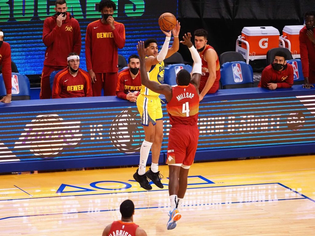 Apr 23, 2021; San Francisco, California, USA; Golden State Warriors guard Jordan Poole (3) scores a three-point basket against Denver Nuggets forward Paul Millsap (4) during the third quarter at Chase Center. Mandatory Credit: Kelley L Cox-USA TODAY Sports