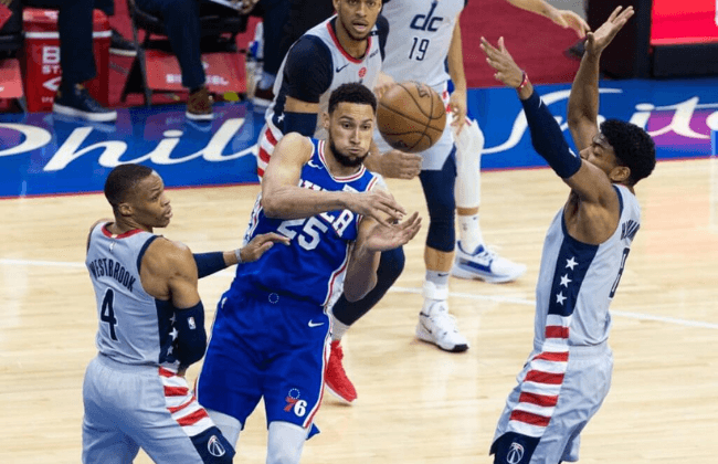 Jun 2, 2021; Philadelphia, Pennsylvania, USA; Philadelphia 76ers guard Ben Simmons (25) passes the ball between Washington Wizards forward Rui Hachimura (8) and guard Russell Westbrook (4) during the first quarter during game five in the first round of the 2021 NBA Playoffs at Wells Fargo Center. Mandatory Credit: Bill Streicher-USA TODAY Sports