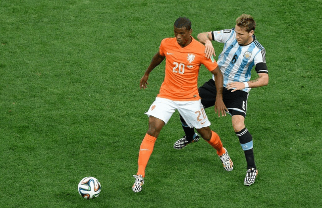 July 9, 2014; Sao Paulo, BRAZIL; Netherlands player Georginio Wijnaldum (20) battles for the ball with Argentina player Lucas Biglia during the semifinal match in the 2014 World Cup at Arena Corinthians. Mandatory Credit: Tim Groothuis/Witters Sport via USA TODAY Sports
