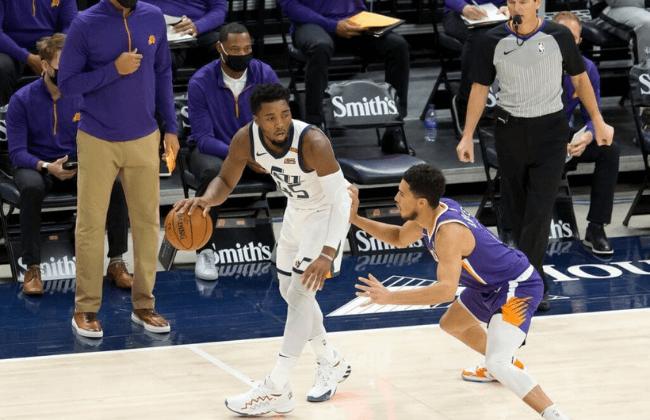 Dec 14, 2020; Salt Lake City, Utah, USA; Utah Jazz guard Donovan Mitchell (45) dribbles the ball as Phoenix Suns guard Devin Booker (1) defends during the first quarter at Vivint Smart Home Arena.