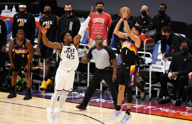 PHOENIX, ARIZONA - APRIL 07: Devin Booker #1 of the Phoenix Suns attempts a three-point shot over Donovan Mitchell #45 of the Utah Jazz during the final moments of the second half of the NBA game at Phoenix Suns Arena on April 07, 2021 in Phoenix, Arizona. NOTE TO USER: User expressly acknowledges and agrees that, by downloading and or using this photograph, User is consenting to the terms and conditions of the Getty Images License Agreement. (Photo by Christian Petersen/Getty Images)