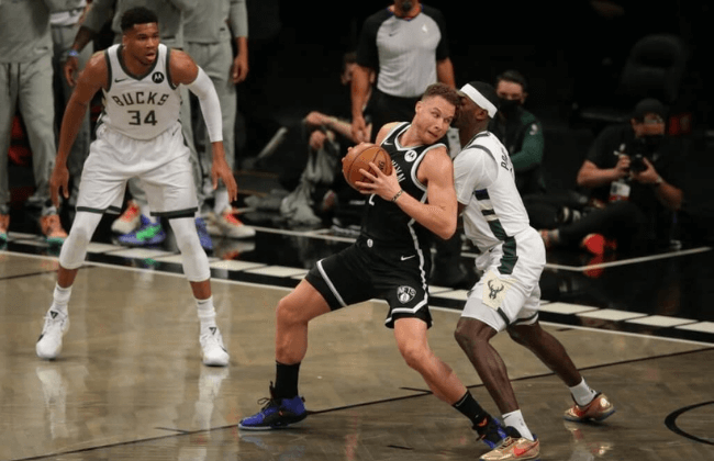 Jun 5, 2021; Brooklyn, New York, USA; Brooklyn Nets power forward Blake Griffin (2) controls the ball against Milwaukee Bucks center Bobby Portis (9) as Bucks power forward Giannis Antetokounmpo (34) looks on during the first quarter of game one in the Eastern Conference semifinals of the 2021 NBA Playoffs at Barclays Center. Mandatory Credit: Brad Penner-USA TODAY Sports