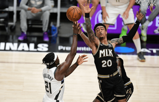 ATLANTA, GA - JuNE 29: John Collins #20 of the Atlanta Hawks blocks the ball against the Milwaukee Bucks during Game 4 of the Eastern Conference Finals of the 2021 NBA Playoffs on June 29, 2021 at State Farm Arena in Atlanta, Georgia.  NOTE TO USER: User expressly acknowledges and agrees that, by downloading and/or using this Photograph, user is consenting to the terms and conditions of the Getty Images License Agreement. Mandatory Copyright Notice: Copyright 2021 NBAE (Photo by Adam Hagy/NBAE via Getty Images)