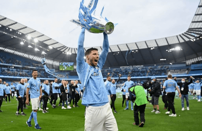 MANCHESTER, ENGLAND - MAY 23: Ruben Dias of Manchester City celebrates with the Premier League Trophy as Manchester City are presented with the Trophy as they win the league following the Premier League match between Manchester City and Everton at Etihad Stadium on May 23, 2021 in Manchester, England. A limited number of fans will be allowed into Premier League stadiums as Coronavirus restrictions begin to ease in the UK.