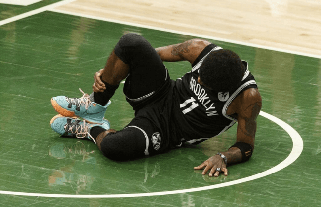 Jun 13, 2021; Milwaukee, Wisconsin, USA; Brooklyn Nets guard Kyrie Irving (11) grabs his leg after being injured during the second quarter against the Milwaukee Bucks during game four in the second round of the 2021 NBA Playoffs. at Fiserv Forum. Mandatory Credit: Jeff Hanisch-USA TODAY Sports