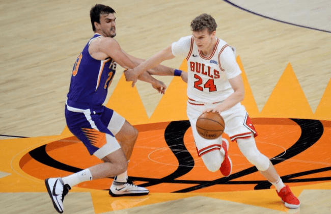 Mar 31, 2021; Phoenix, Arizona, USA; Chicago Bulls forward Lauri Markkanen (24) dribbles against Phoenix Suns forward Dario Saric (20) during the second half at Phoenix Suns Arena. Mandatory Credit: Joe Camporeale-USA TODAY Sports
