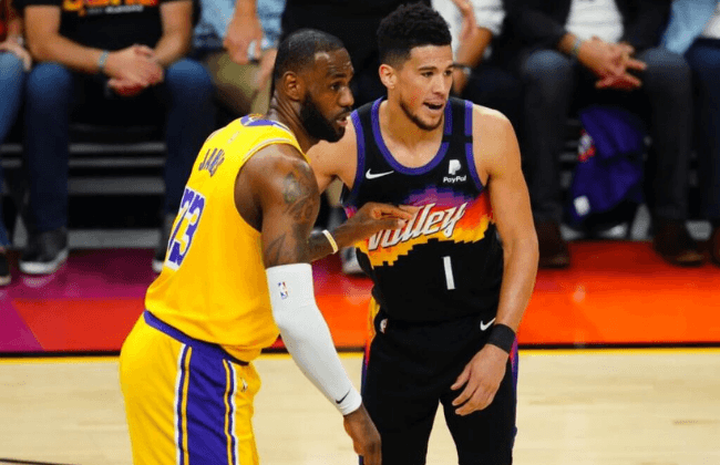 May 25, 2021; Phoenix, Arizona, USA; Los Angeles Lakers forward LeBron James (23) against Phoenix Suns guard Devin Booker (1) during the second half in game two of the first round of the 2021 NBA Playoffs at Phoenix Suns Arena. Mandatory Credit: Mark J. Rebilas-USA TODAY Sports