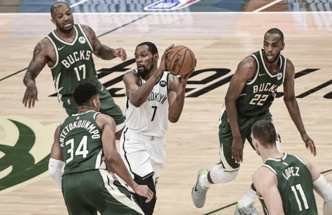 Jun 10, 2021; Milwaukee, Wisconsin, USA; Brooklyn Nets forward Kevin Durant (7) holds onto the ball while guarded by Milwaukee Bucks forward Giannis Antetokounmpo (34), forward P.J. Tucker (17), center Brook Lopez (11) and forward Khris Middleton (22) in the third quarter during game three in the second round of the 2021 NBA Playoffs at Fiserv Forum. Mandatory Credit: Benny Sieu-USA TODAY Sports