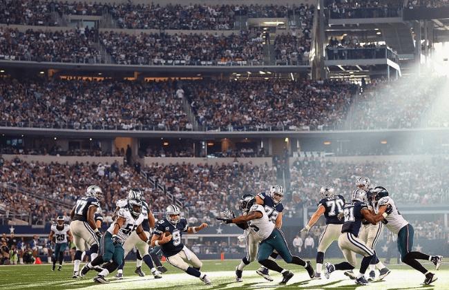 ARLINGTON, TX - NOVEMBER 27:  Tony Romo #9 of the Dallas Cowboys holds the ball under pressure from the Philadelphia Eagles at Cowboys Stadium on November 27, 2014 in Arlington, Texas.  (Photo by Ronald Martinez/Getty Images)