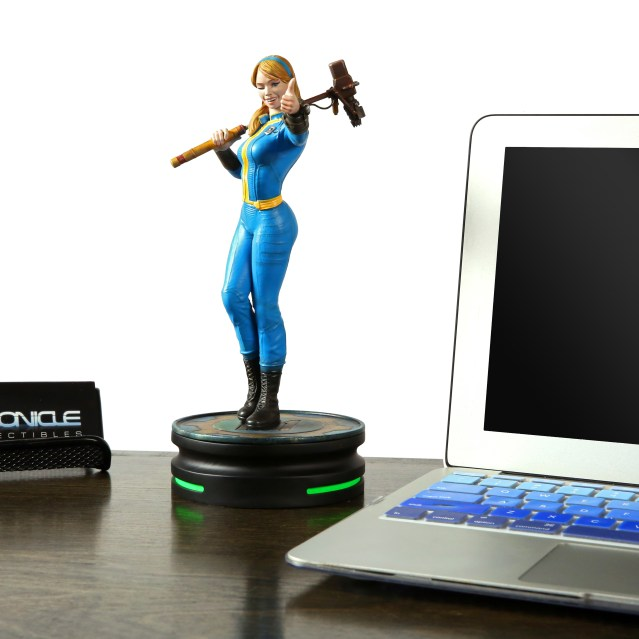 A Vault Girl statue from Fallout. The statue is slightly taller than what appears to be an open 13 inch macbook air, including its pedestal. Image from THINKGEEK.com https://www.thinkgeek.com/product/ktgg/