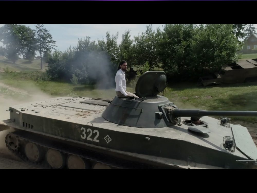 Richard La Ruina, wearing a white dress shirt and tan pants sits atop a tank against an outdoor backdrop. Super Seducer 2, RLR Training Inc, Red Dahlia Interactive, 2018