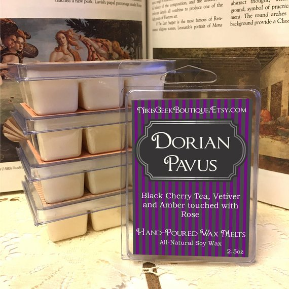 """An image of several wax melts. The package reads, """"NikisGeekBoutique.Etsy.com. Dorian Pavus. Black Cherry Tea, Vetiver and Amber touched with Rose. Hand-Poured Wax Melts. All-Natural Soy Wax."""""""
