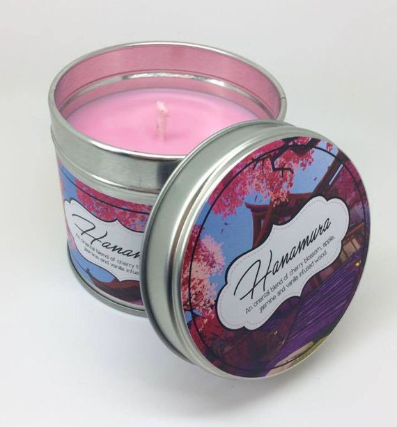 """An image of a pink candle. The label, which has a screenshot of the Hanamura map from Overwatch, reads, """"Hanamura. An oriental blend of cherry blossom, apple, jasmine and vanilla infused wood."""""""