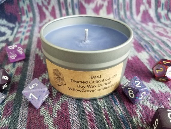 "A photo of a Bard-themed candle, which is purple. The label reads, ""Bard Themed Critical Candle. Soy Wax Candle. WillowGroveCandles.com."""