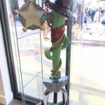 """A keyblade with the blade made out of a green cactus wrapped in a rope and a bandana, wearing a brown wide-brimmed hat. A badge reading """"Sheriff"""" is attached to the blade. The handle has the shape of a rocketship with Buzz Lightyear's white and blue motif. The keyblade sits in a glass case at Disney Springs. Kingdom Hearts Pop-Up, Disney Springs, 2018"""