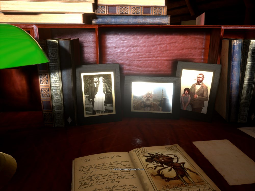 "A screenshot of What Never Was depicting a desk containing several photos and books. A green glass bankers lamp peeks into the left of the frame, and the desk is made of rich red wood. A notebook is open, and the three photos propped up against the back of the desk are framed and look old. Text at the bottom of the screen reads ""I...I know you have questions for me."""
