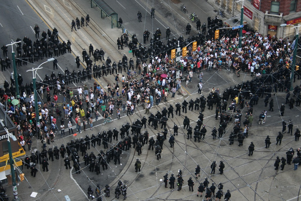 A photo of riot police encircling protests as the G20 Protests in Toronto, 2010.
