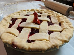 Photo of a pie bird, a device that supports a pie crust and allows air to vent out of a pie, sticking out of a blackberry-filled, lattice-top crust pie. The pie sits next to a rolling pin.