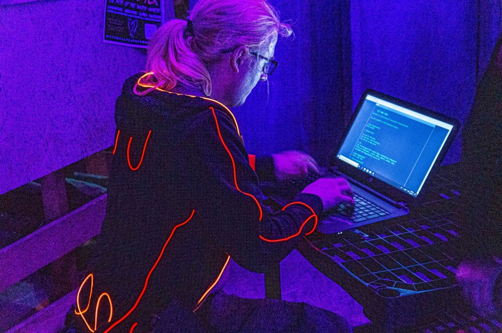 A player in an LED-clad costume looks with concentration at a laptop screen, which shows the in-game hacking interface.