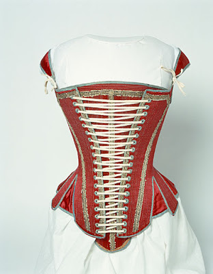 English stays, dated to 1620-1640. It's made out of linen and red silk satin and edged with pale blue silk ribbons. It's laced in the front over a boned stomacher. From the Manchester Galleries Collections.