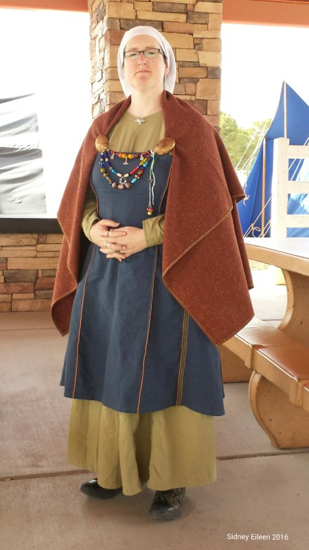 Blue Linen Viking Apron Dress, quick photo while at an event. Linen apron dress and underdress, hand stitched and embroidered with linen thread, square wool cloak edged with linen embroidery.