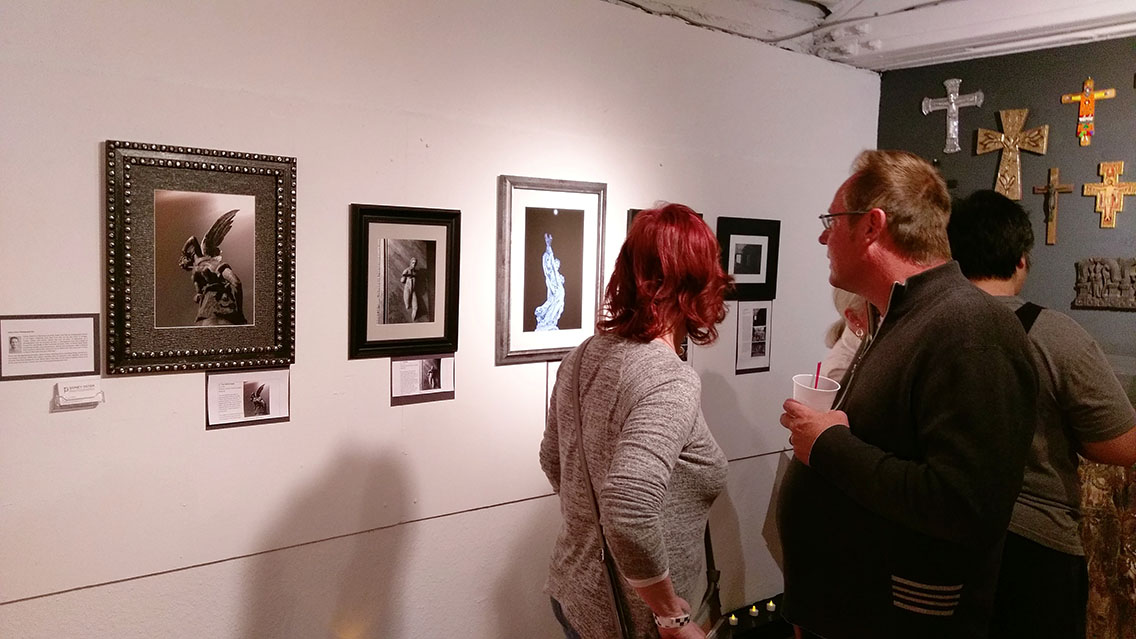 Guests looking at photographs at art exhibit