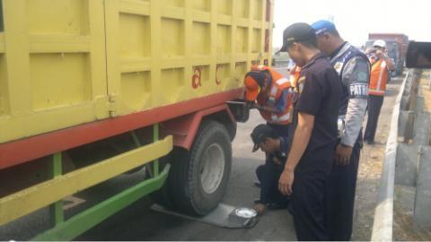 Petugas Jasa Marga saat mengecek truk bermuatan yang akan melintasi tol di pintu masuk tol Porong.