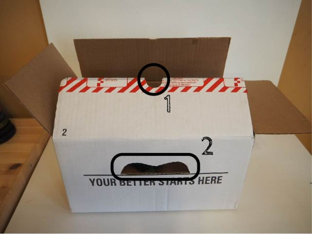紙箱上切出兩個洞,紙箱上方切一個放手電筒的小洞、紙箱前方切一個小視窗。