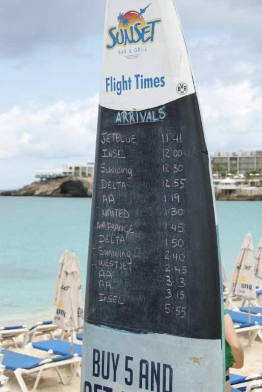 Maho Beach Surfbrett mit den Ankunftszeiten der Flugzeuge auf Sint Maarten