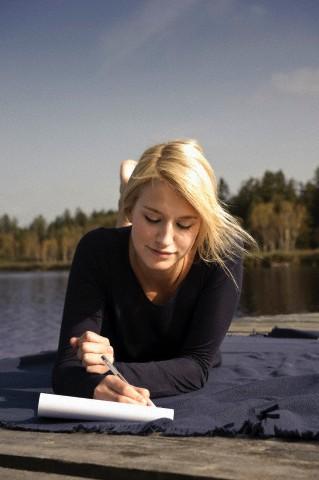 Young woman lying on blanket,writing